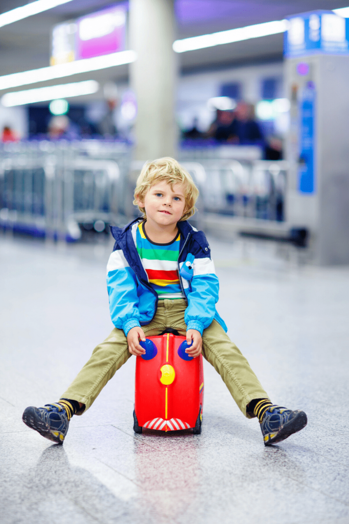What do you do if your flight is delayed when you are travelling with small children? Child sitting on suitcase in a departure hall