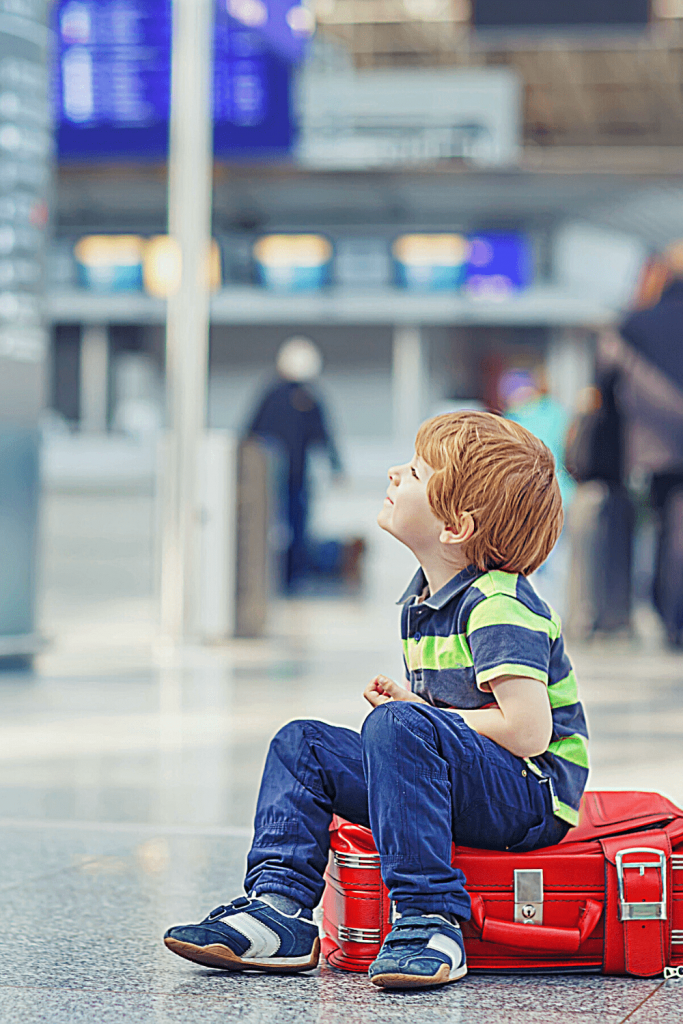 What do you do if your flight is delayed and you are travelling with young children? Child sitting on a suitcase in the departure hall looking bored