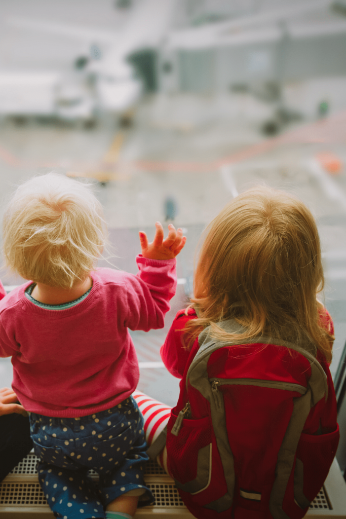 What to do if your long-haul flight with young kids is delayed: two young children looking out of a window at the airport