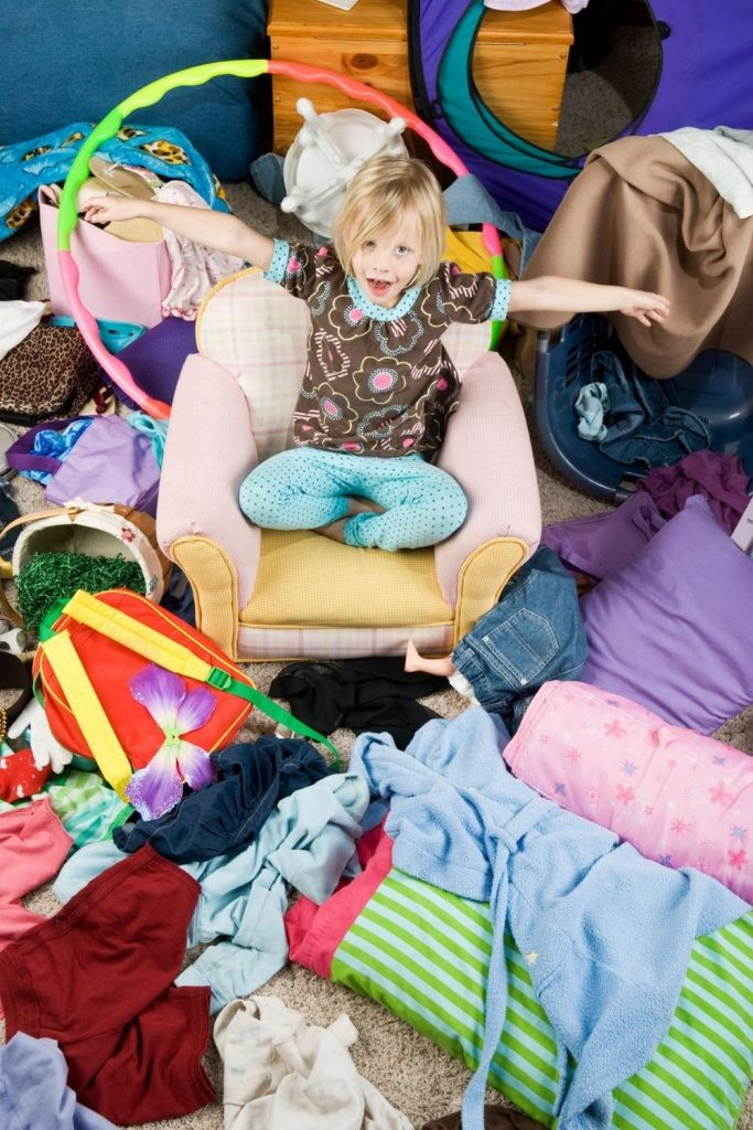 I'm a hot mess mum and that often means my house looks like a bomb exploded. It may be untidy but it is normally clean. Child sitting in the middle of a mess of clothes and toys, etc.