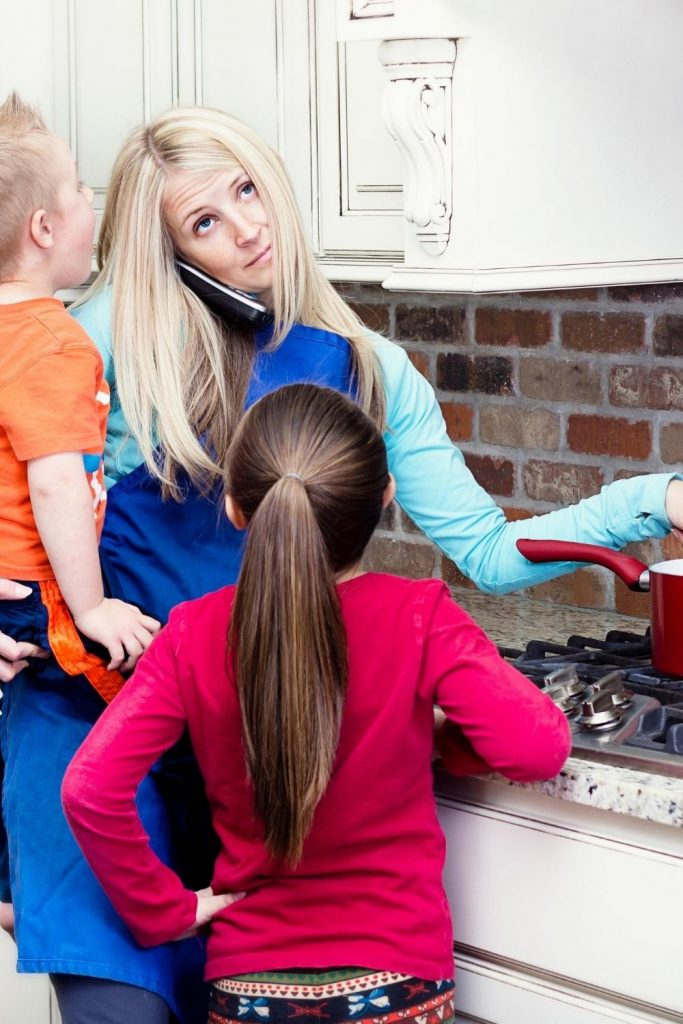When you're a hot mess mum, you always seem to be doing everything at once and succeeding at nothing. Mum on phone while stirring a pot with child on her hip and another asking a question.