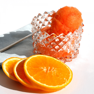 A bowl of Aperol and blood orange sorbet and slices of orange