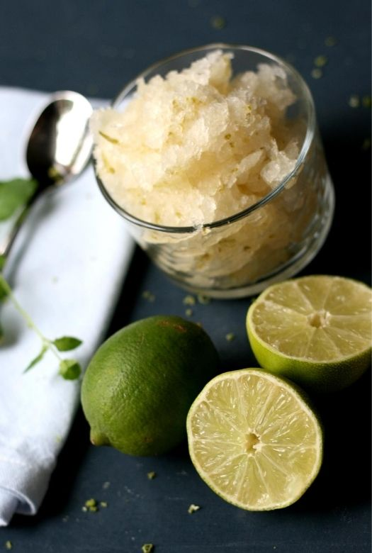 Refreshingly simple caipirinha sorbet, on a diagonal with limes, a serviette and spoon