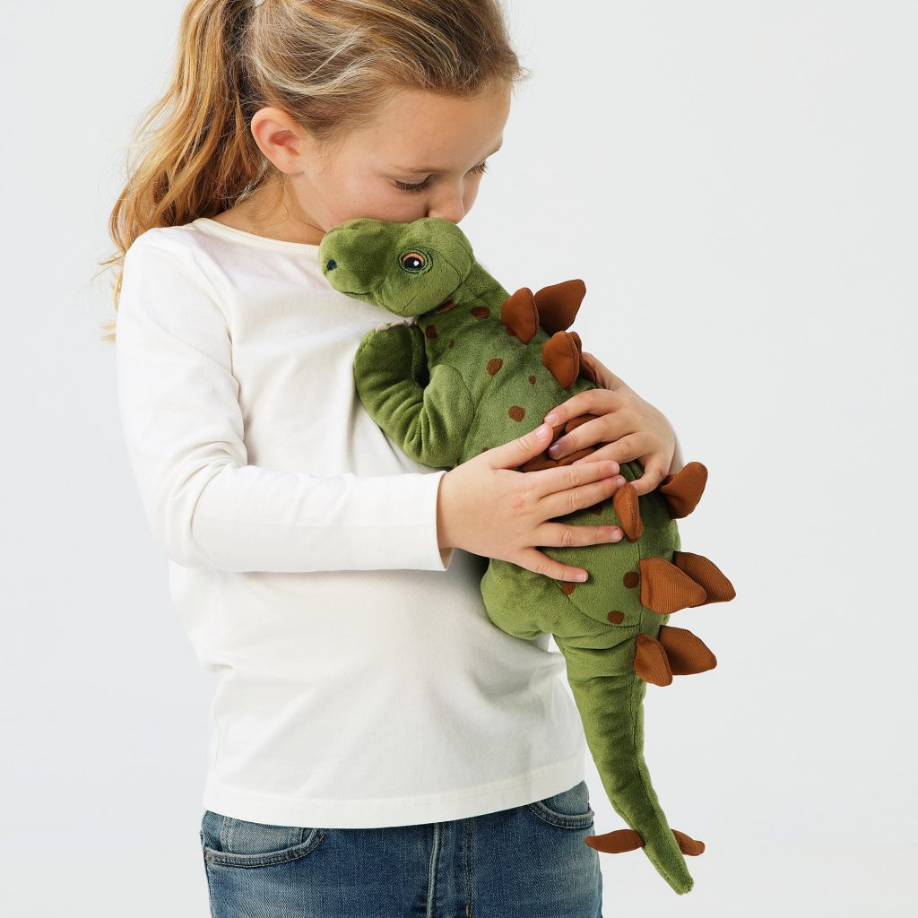 50+ cool dinosaur gifts for girls who love dinosaurs: IKEA had gotten in on the act with its new JÄTTELIK range of bedding and bedroom decor and stuffed toys. Image of new JÄTTELIK stegosaurus, held by a little girl; image ikea.com.