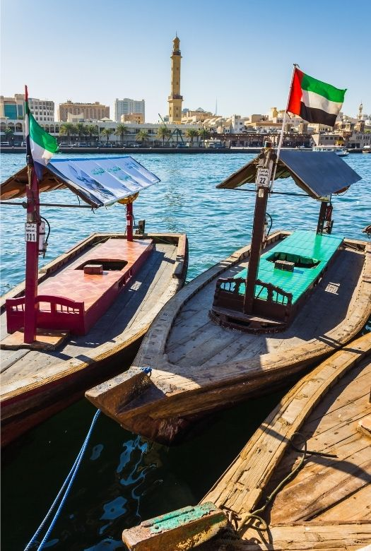 What you need to know before visiting Dubai with kids: Know when the national holidays are. He Abras on the Dubai creek with national flags