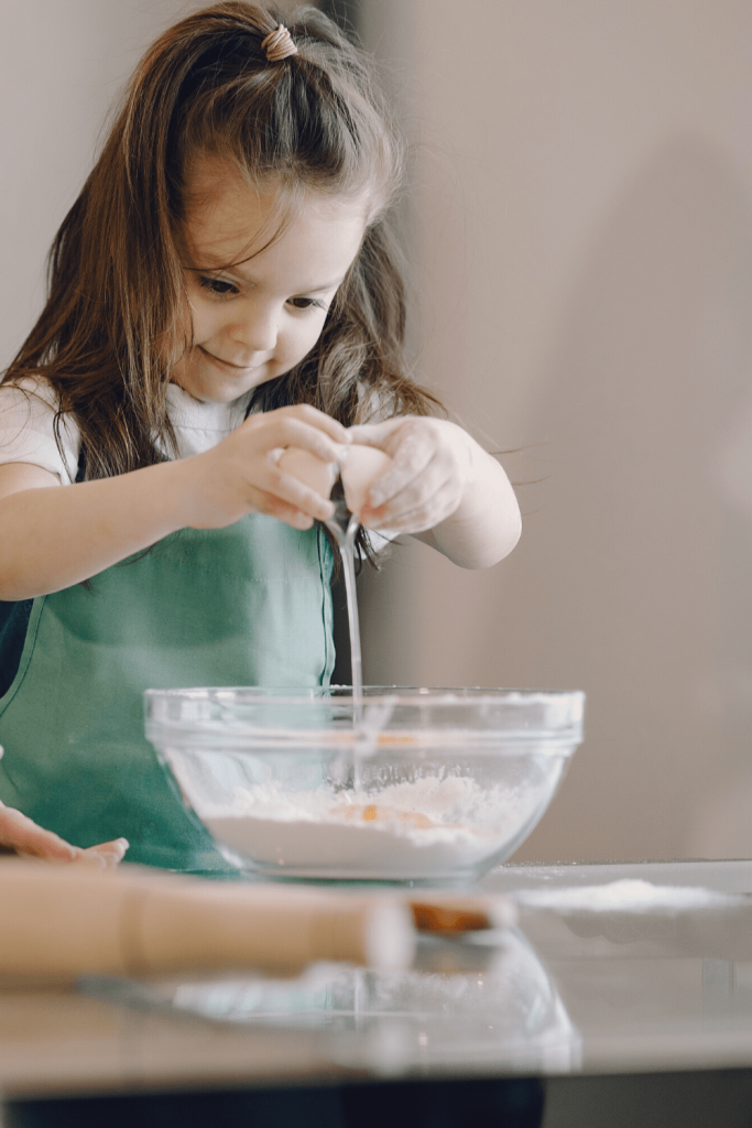 Top tips for baking with kids: child cracking an egg
