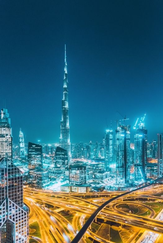 What you need to know before visiting Dubai with kids: you will really want to know about car seats (here image of the skyline and main roads of Dubai at night)
