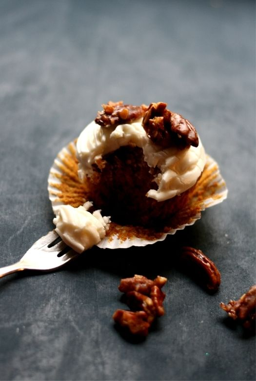 Sweet potato cupcake with marshmallow cream cheese frosting, half eaten with fork and caramelised pecans