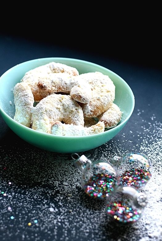 Bowl of vanille Kipferl with powdered sugar and Christmas baubles strewn around