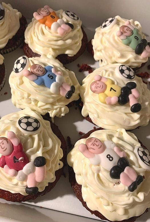 Red velvet cupcakes with white chocolate cream cheese frosting with soccer players and soccer balls as decoration