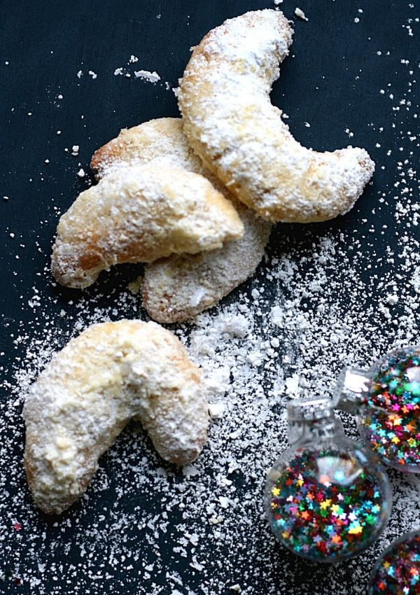 A small pile of vanille Kipferl, or vanilla crescents, with icing sugar and Christmas baubles.