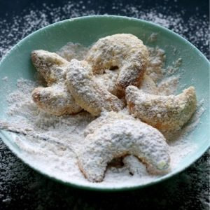 Bowl of fresh Vanille Kipferl, being dusted with powdered sugar