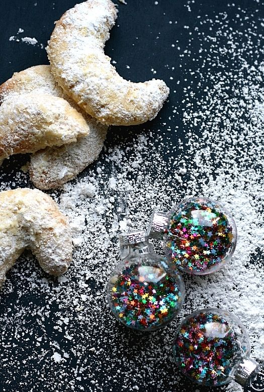 Small pile of vanille Kipferl or vanilla crescents with powdered sugar and Christmas baubles
