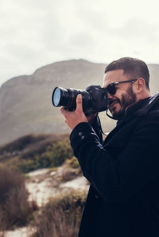 Great gifts for travel lovers when they can't travel: gift a photography course to improve their skills before their next trip (image of man taking a photo)