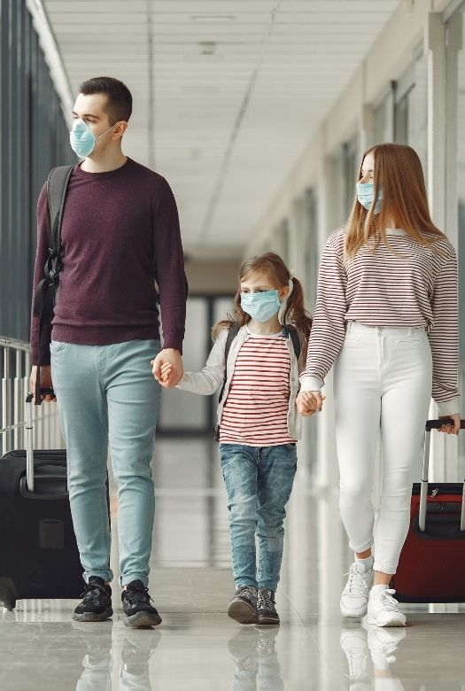 Ultimate 2020 gift guide for travel lovers: give them a first aid kit, with 2020 travel essentials such as face masks and additional disinfectant. Here a family of 3 wearing face masks, at an airport