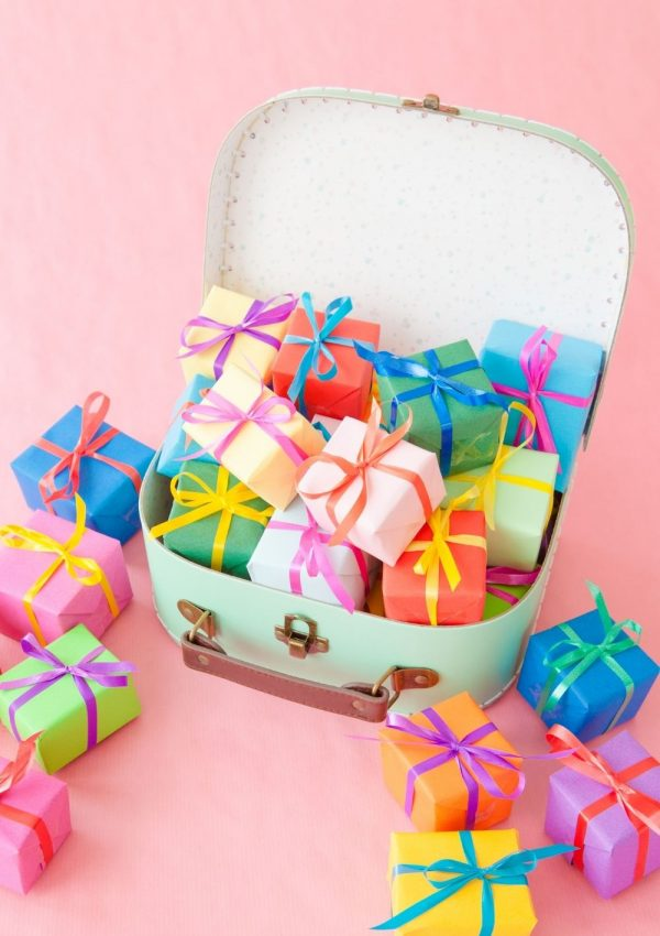 Great gifts for travel lovers when they can't travel - a suitcase full of brightly wrapped presents