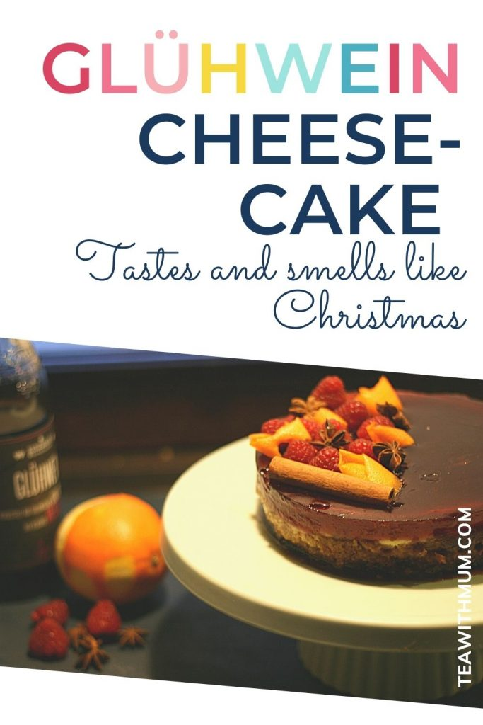 PIN: Glühwein Cheesecake: Tastes and smells like Christmas; with image of a Glühwein cheesecake on a cake stand with an orange and raspberries and a bottle of Glühwein
