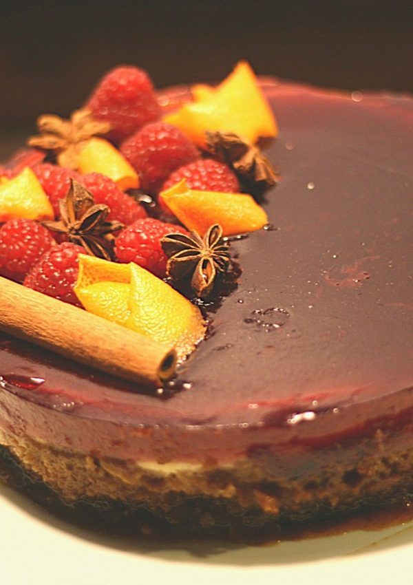 Glühwein cheesecake, with chai base, creamy cheesecake filling and Glühwein glaze, decorated with orange peel, cinnamon sticks, star anise and fresh raspberries