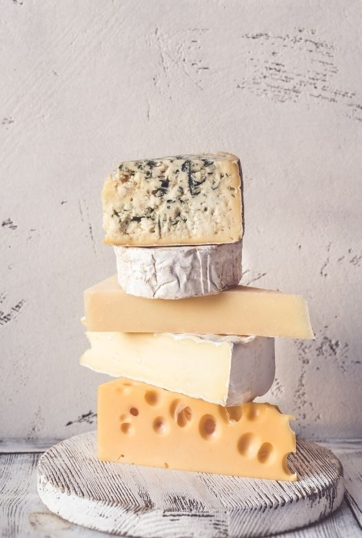 Looking for great gifts for travel lovers when they can't travel? Why not try a subscription box, such as for international cheeses. Buy or make one yourself. (Various cheeses stacked on one another)