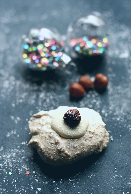 A German hazelnut macaroon (Hazelnuss Makronen) with some hazelnuts and Christmas baubles