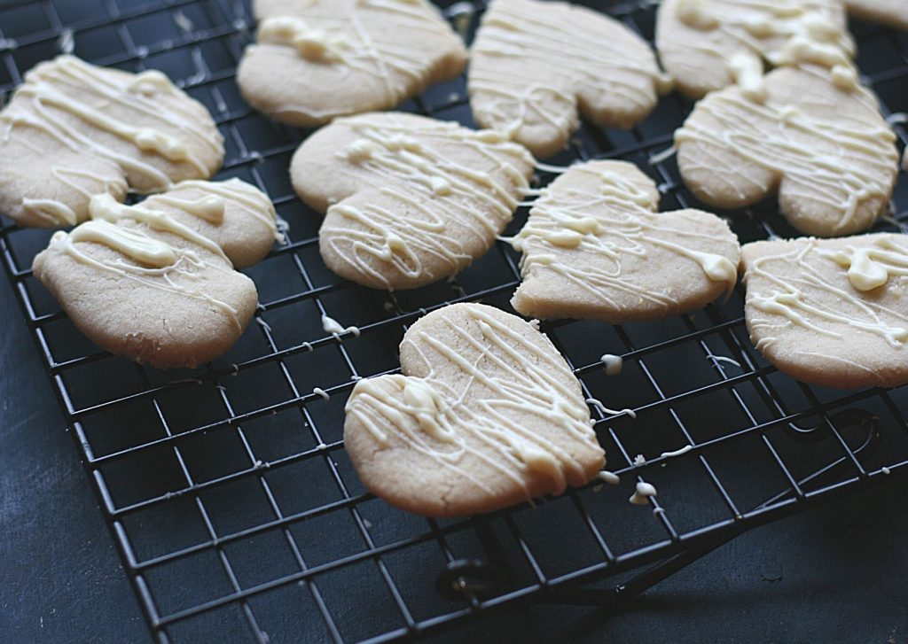 Tea-infused shortbread hearts on a wire wrack, drizzled with white chocolate