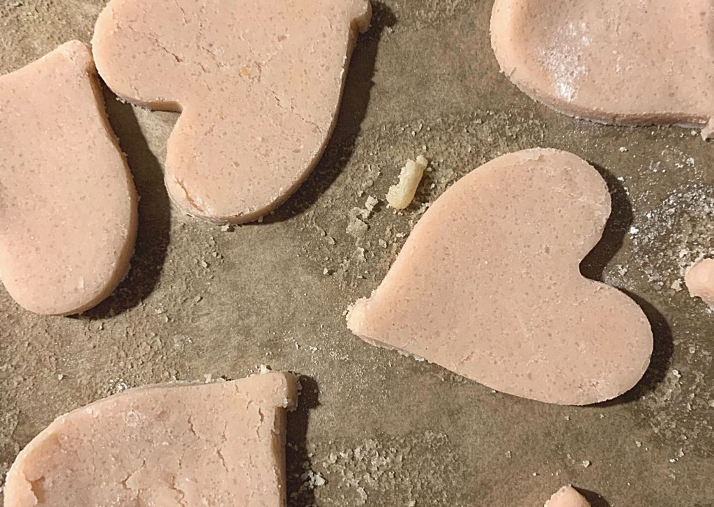 Pale pink tea-infused shortbread hearts, on a baking tray about to go into the oven