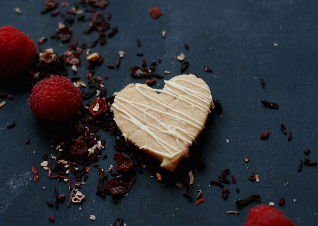 A simple and delicious tea-infused shortbread heart, drizzled with white chocolate, pictured with fresh raspberries and loose tea