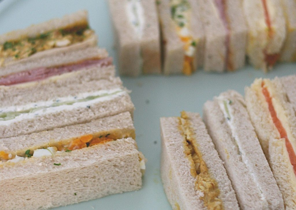 Easy and elegant afternoon tea finger sandwiches on a green stand: ham and mustard, smoked salmon and lemon butter, cucumber and mint cream cheese, egg salad and cress and coronation chicken.