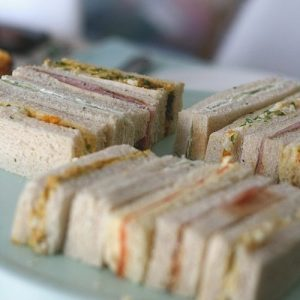 Close up of 5 different traditional afternoon tea finger sandwiches on a green tray