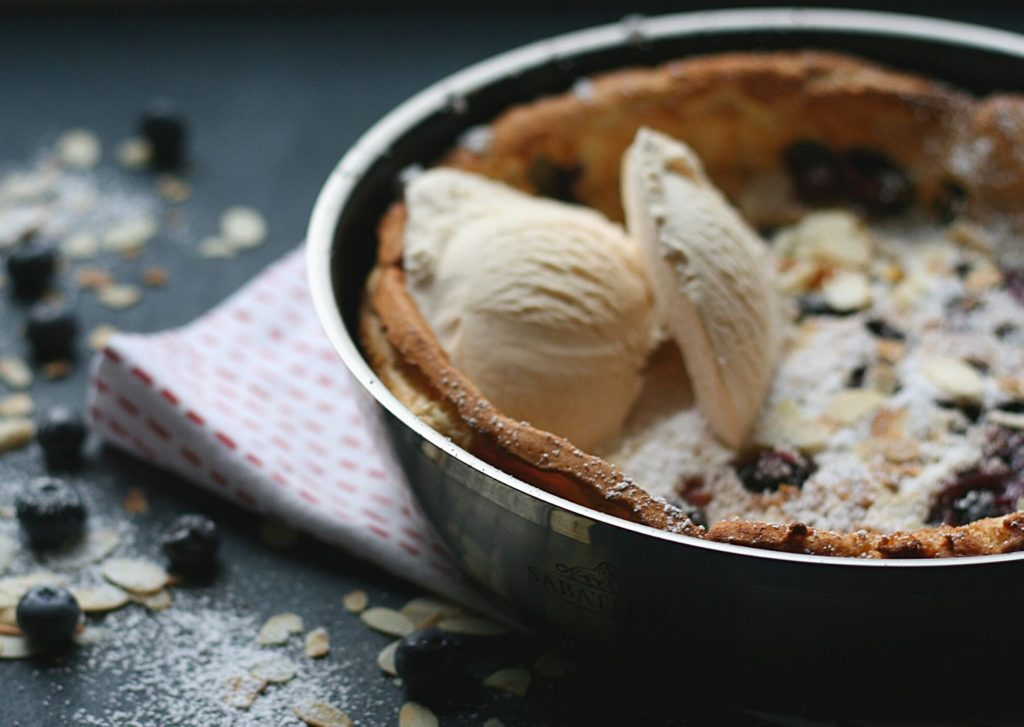 Dutch baby pancake - German pancake - Bavarian blueberry pancake with vanilla ice cream, toasted almond flakes and powdered sugar still in the frypan.