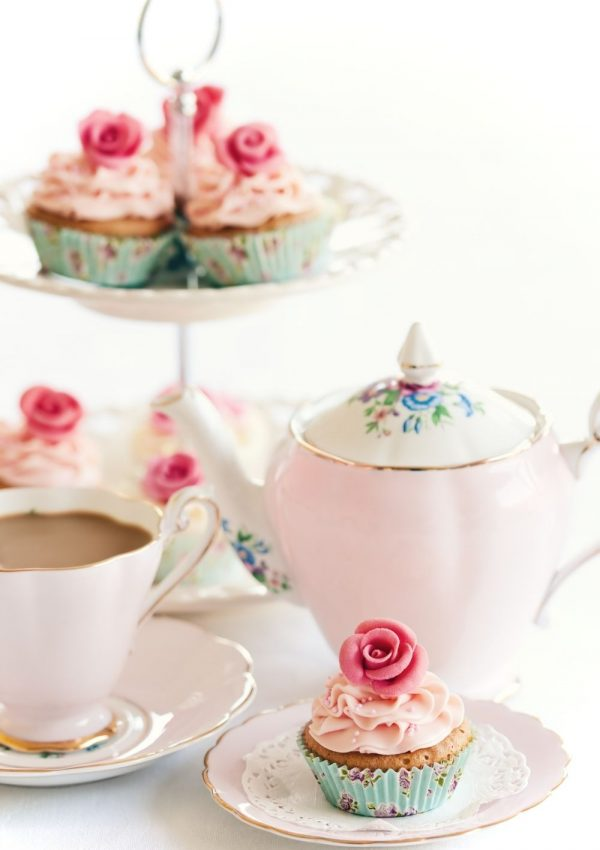 The quintessential English afternoon tea: A lovely pink tea pot with tea served in dainty tea cups and a plate and stand with cupcakes decorated with roses. The finger sandwiches and scones have obviously been cleared away.