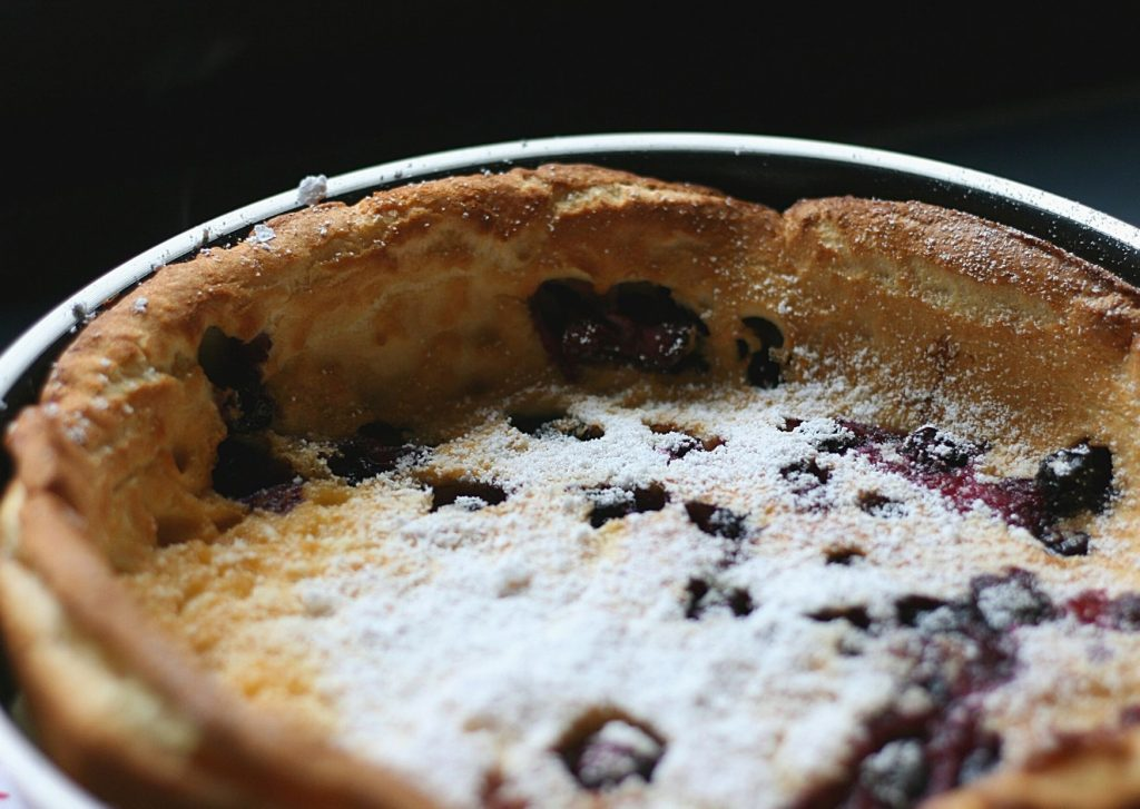Bavarian blueberry pancake with powdered sugar, still in the frypan
