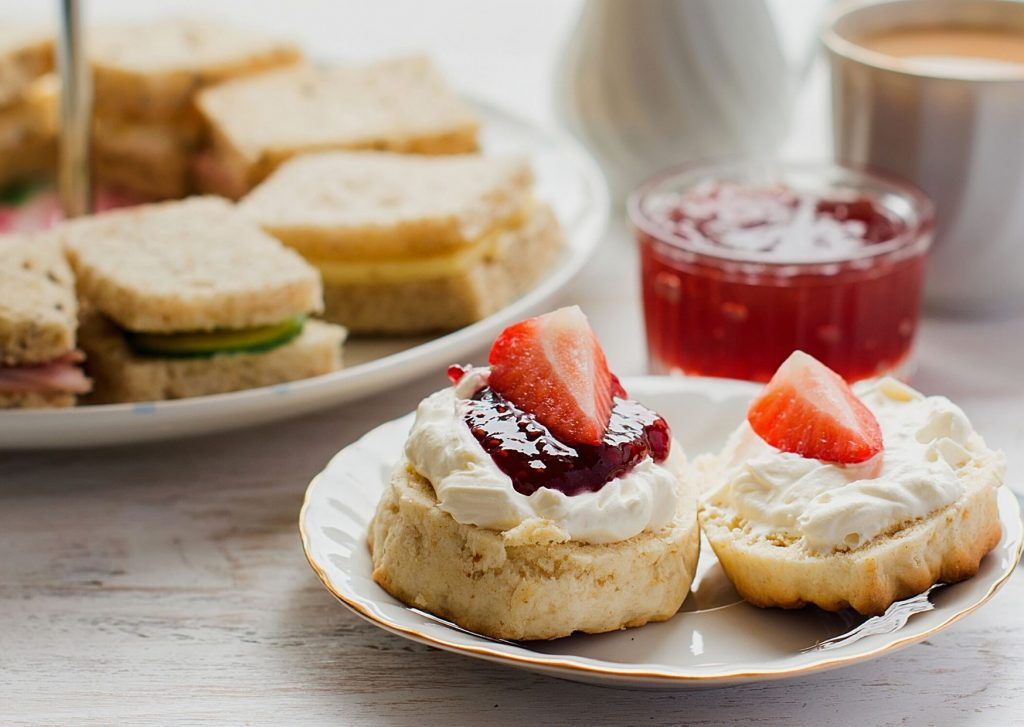 The quintessential English afternoon tea, with fresh scones with preserves and clotted cream, and a plate of finger sandwiches in the background.
