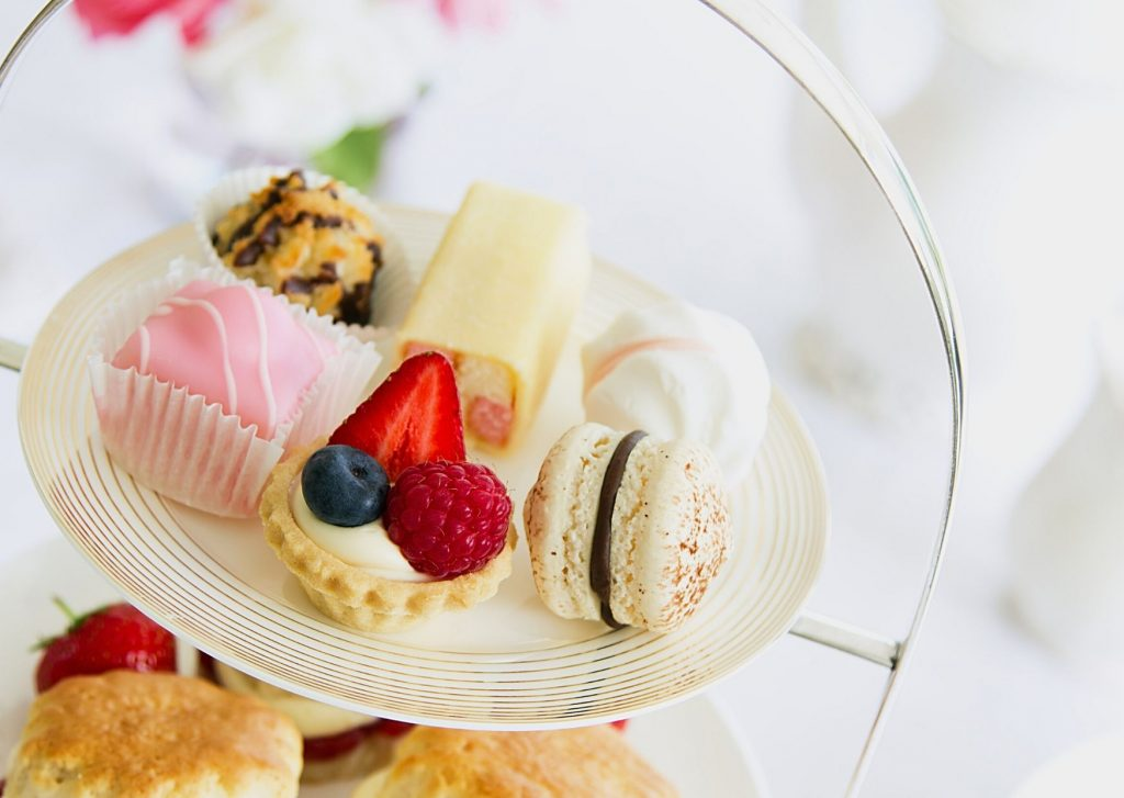 Traditional English afternoon tea - with a stand with fresh scones with preserves and clotted cream, and a level of small cakes and sweets.