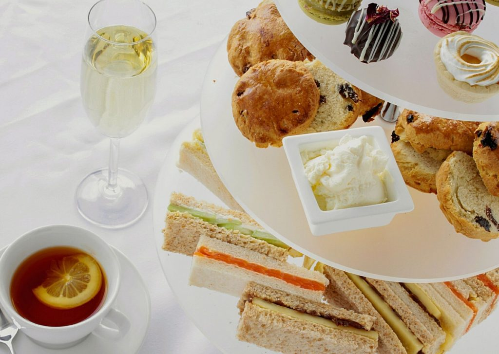 Three-tiered stand with the traditional English afternoon tea menu: finger sandwiches, scones with preserves and clotted cream, small cakes