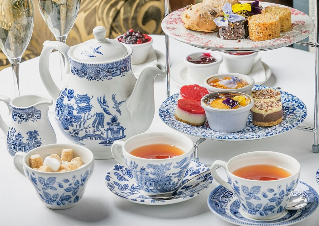 The quintessential English afternoon tea - with a pot of tea, cups of tea, small cakes and desserts