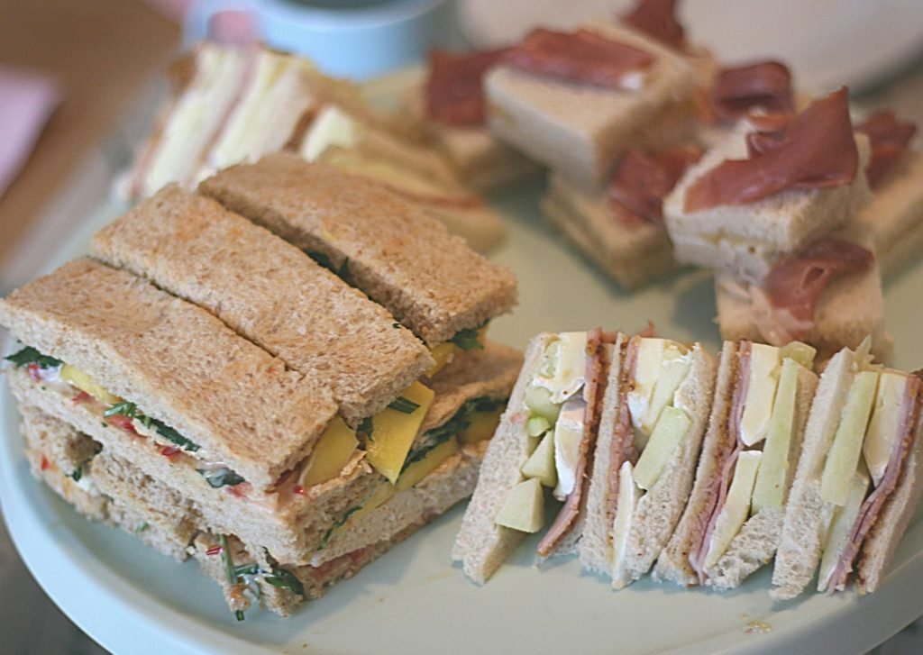 Afternoon tea sandwiches with a fruity twist, featuring our ham, mustard, brie and apple sandwiches, mascarpone, fig compote and prosciutto sandwiches and grilled chicken, mango and sweet chili sandwiches