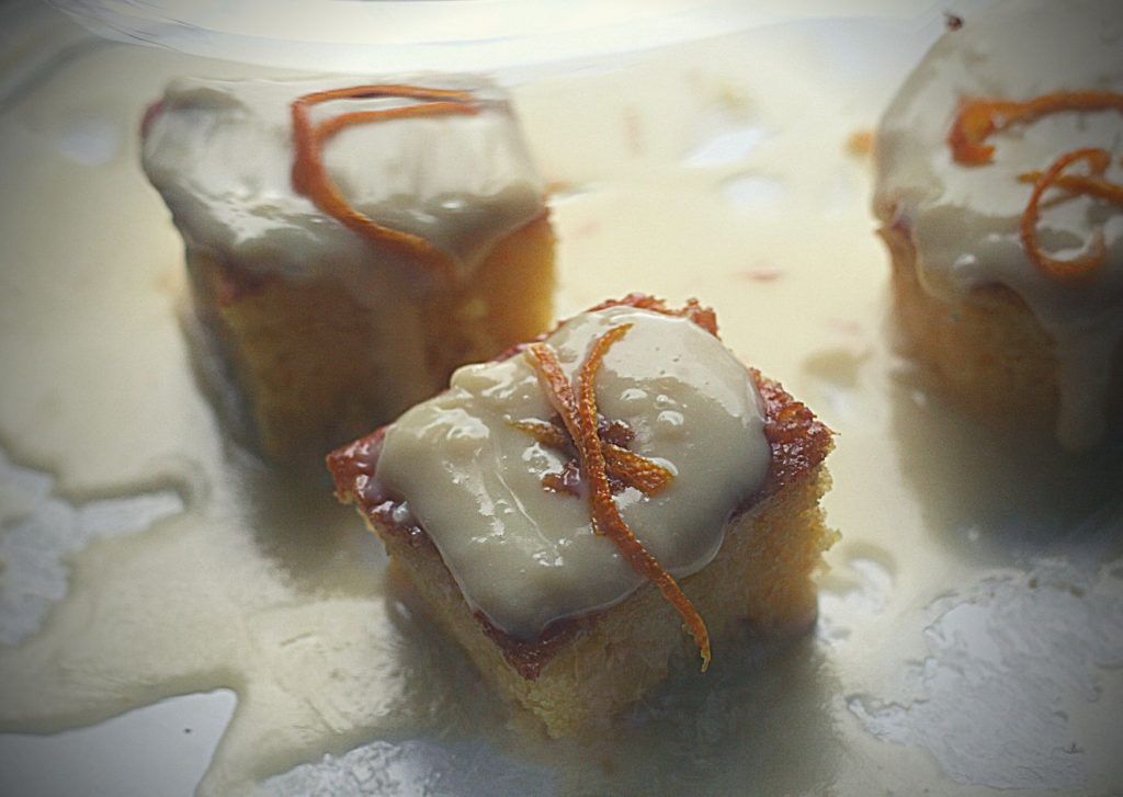 Two square and one round orange and white chocolate petit fours, with orange peel, on a cake stand