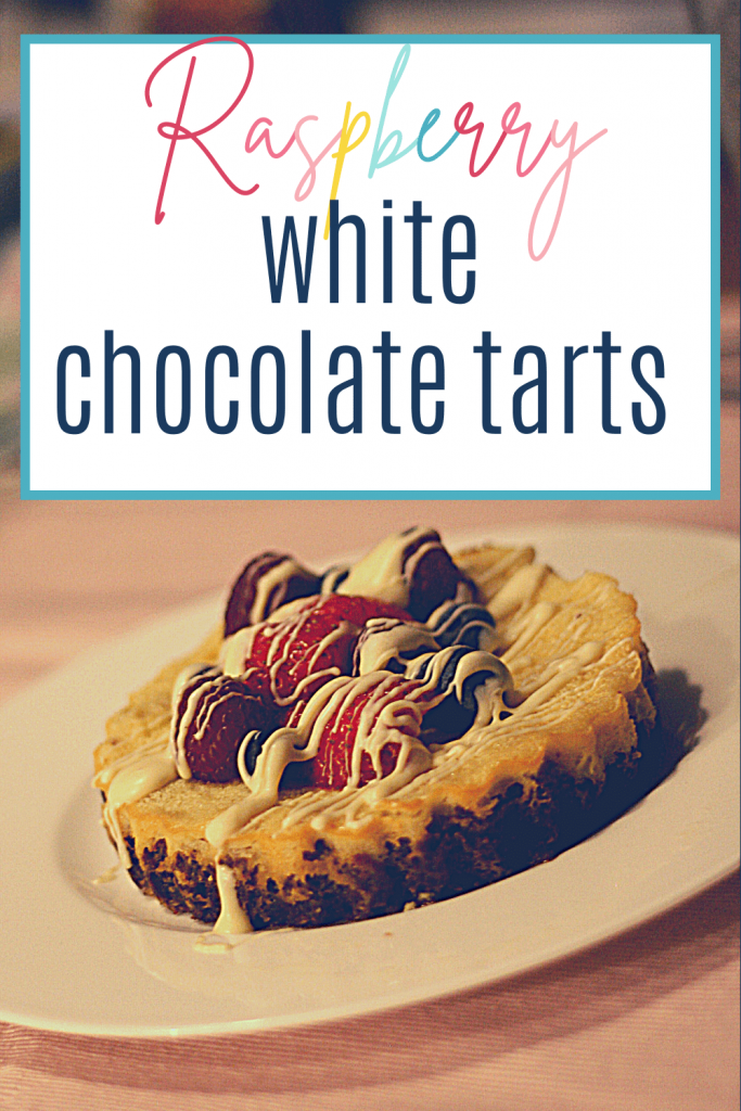Pin: Raspberry white chocolate tarts, with an image of a mini white chocolate cheesecake with fresh raspberries, strawberries and blueberries and white chocolate drizzle