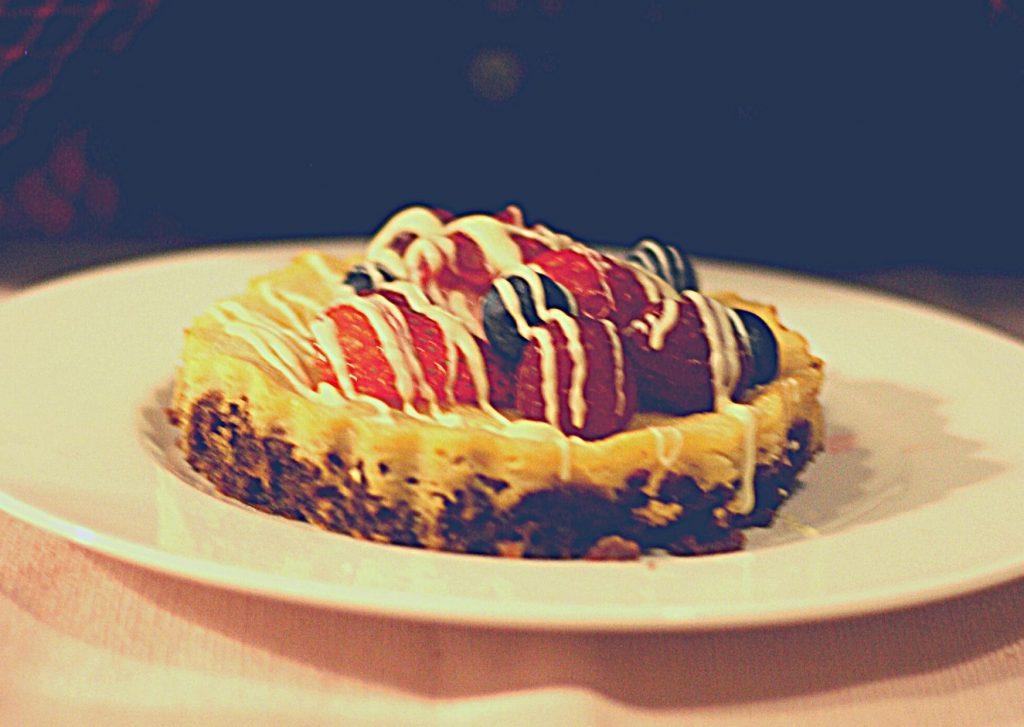 White chocolate tart with fresh strawberries, raspberries and blueberries and white chocolate drizzle