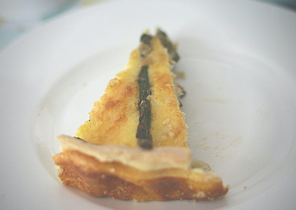 A slice of quiche aux asperges, from above, on a white plate