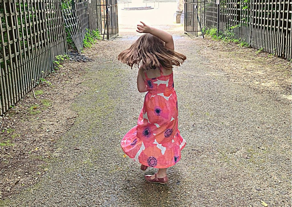 Miss M dancing near Colonades Grove in the garden at Versailles, proof that it is a good idea to visit Versailles with kids