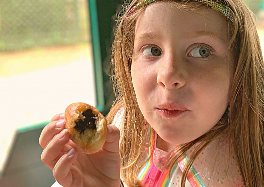 Miss M eating a beignet on the petit train at Versailles (we were supposed to share)