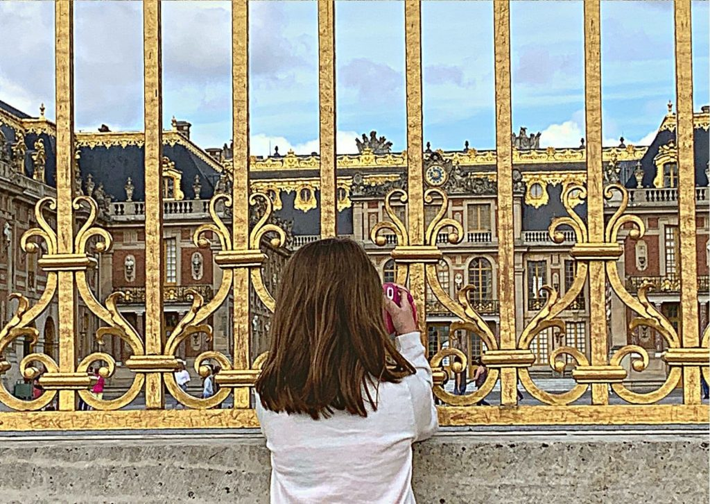 Miss M photographing the Palace of Versailles through the gold front gates