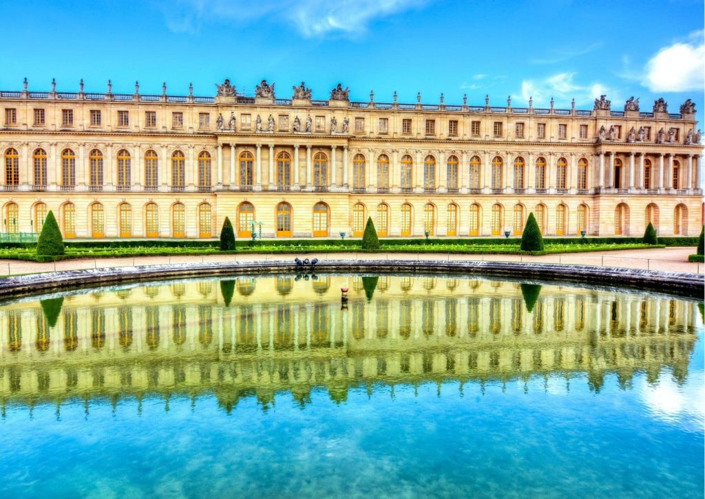 The Palace of Versailles, from the gardens, reflected in one of the (many) fountains