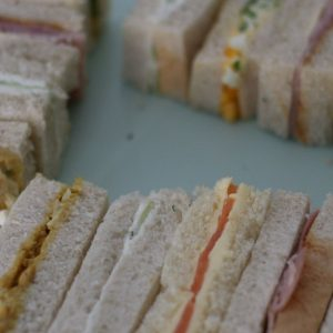 Close up of easy and elegant afternoon tea finger sandwiches on a green stand: ham and mustard, cucumber with mint and chive cream cheese, smoked salmon with lemon butter, egg and cress and coronation chicken.