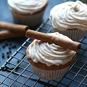 Chai cupcakes with spiced cream cheese frosting decorated with a cinnamon stick, on a rack, with 2 other cupcakes, cinnamon sticks and peppercorns