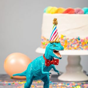 50+ dinosaur gifts for girls who love dinosaurs: T-Rex with birthday hat and cake